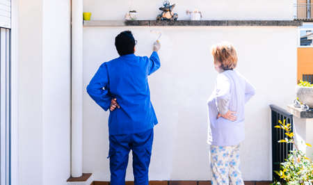 Foto de Man and woman paint the wall of the house terrace. Back view of mature couple reforming the home. - Imagen libre de derechos