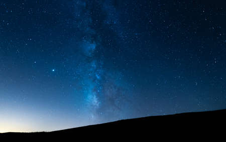 Photo for Milky way up a hill in a starry night sky. Blue sky with stars without light pollution. - Royalty Free Image