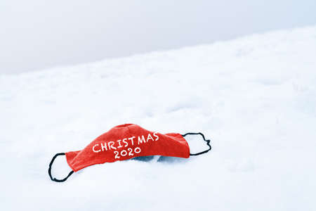 Photo pour Christmas 2020. Red medical face mask on top of a snowy ground. Concept of covid-19 pandemic usable for background or poster for the 2020 winter and christmas campaign. - image libre de droit
