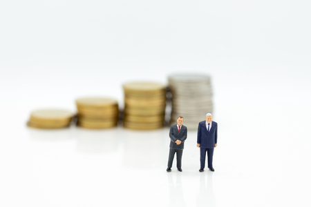 Miniature people:  Businessman standing with stack of coins. Image use for business concept.