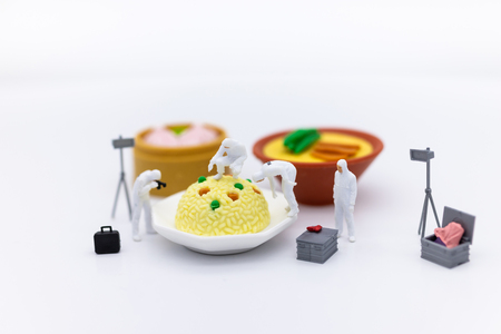 Miniature People and food, check the nutritional value, nutrients received in each meal. Image use for food and beverage concept.