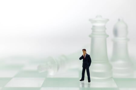 Miniature people: Businessman standing on the chess game, thinking solution for the business game, use as a business competition concept.