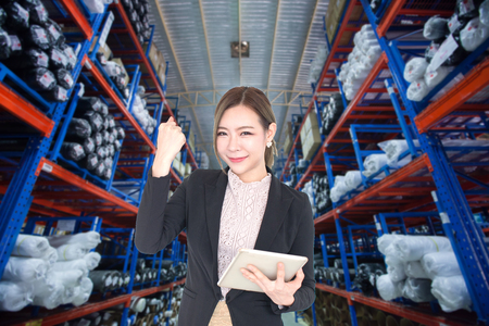 Young Asian business woman using tablet smart phone technology with warehouse factory on background and copy space