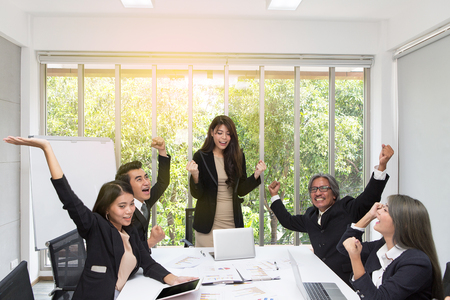 Foto de Group of happy business people cheering in office. Celebrate success. Business team celebrate a good job in the office. Asian people. - Imagen libre de derechos