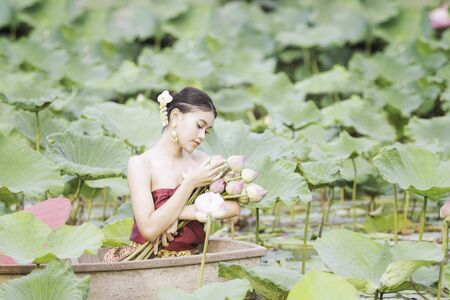 Photo pour Women wearing Thai dresses are admiring lotus flowers. Asian women sitting on wooden boats to collect lotus. Beautiful girl wearing traditional Thai dress hand holding a flowers. - image libre de droit