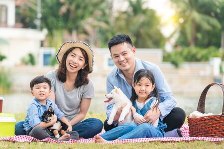 Foto für An Asian family plays with a Shiba Inu dog. Family has father, mother and son, daughter. Picnicking in the garden. - Lizenzfreies Bild