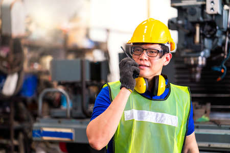 Photo pour Portrait of an engineer at work in the industry. Foreman works with radio to communicate. Professional technicians work through the radio. In factories that have machinery - image libre de droit