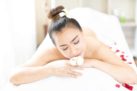 Photo pour Asian woman relaxing with floral scent in spa massage parlor. - image libre de droit