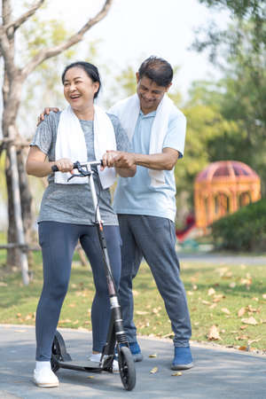 Photo for An elderly couple is teaching his wife to play a scooter. Sporty mature couple staying fit with sport. - Royalty Free Image