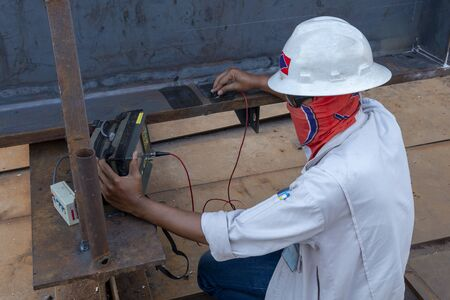 Photo for The inspectors are checking defect in welded of steel add joint with process Ultrasonic testing (UT) of Non-Destructive Testing(NDT) at industrial factory. - Royalty Free Image