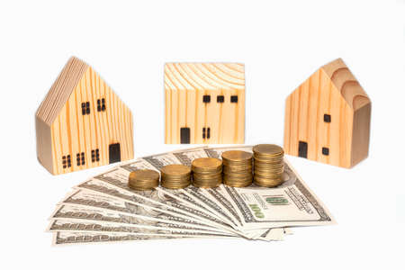 Photo pour Stacked coin on US dollar bills and three wooden house, isolated on white background. - image libre de droit