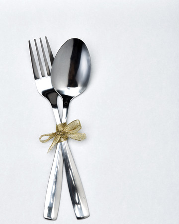 Photo pour Fork and spoon with gold ribbon on white background - image libre de droit