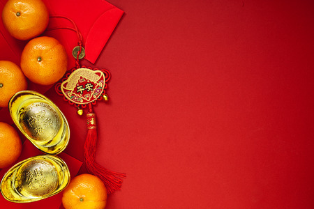 Photo pour Chinese coins of luck or chinese knot and Chinese gold ingots and Traditional chinese knot  (Foreign text means blessing) and Red envelopes and decoration with Fresh oranges on Red Paper background - image libre de droit