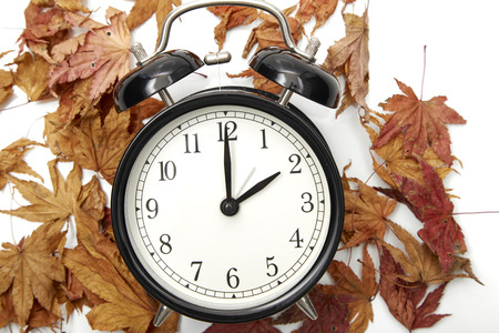 Foto per Image of autumn Time Change, Fall back concept, Dry leaves and vintage alarm Black Clock on wooden table outdoors at afternoon,for text - Immagine Royalty Free