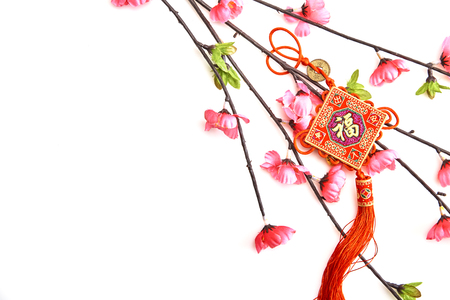 Photo pour Plum Pink Cherry Branch with Chinese Lucky Knot on white background Chinese New Year decorations (English translation for foreign text means blessing) - image libre de droit