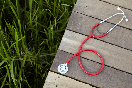 Photo pour stethoscope red on wood, Concept, Doctor or medical volunteers to visit elderly people in rural Asia - image libre de droit