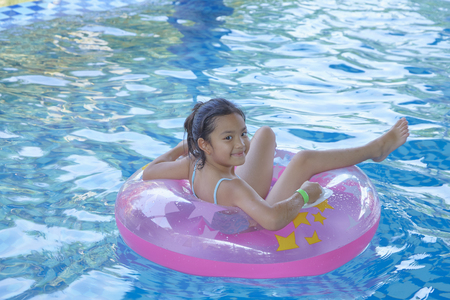 Photo pour Asian Girl (9-10) sitting on pink inflatable ring in swimming pool, summer vacation concept - image libre de droit