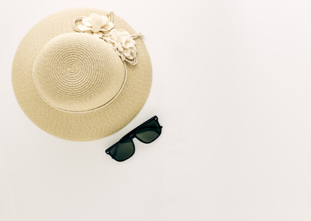 Summer holiday background, flat lay beach women's accessories: straw hat, headphones, sunglasses on white background, with empty space for text. Travel and fashion concept. Vacation summer sales.