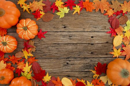 Foto de Autumn multicolored  leaves and pumpkins old brown wood table background with copy space, flat lay, minimal concept - Imagen libre de derechos