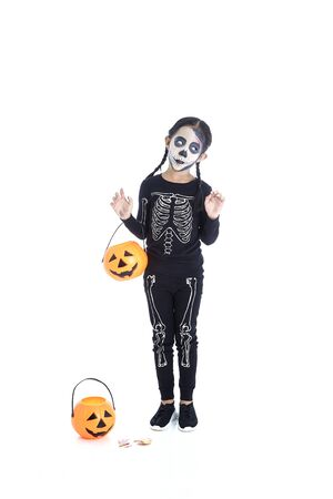 Foto de Happy asian little girl holding jack o lantern pumpkin basket in halloween skeleton costume isolated on white background, Concept for Halloween holiday. - Imagen libre de derechos
