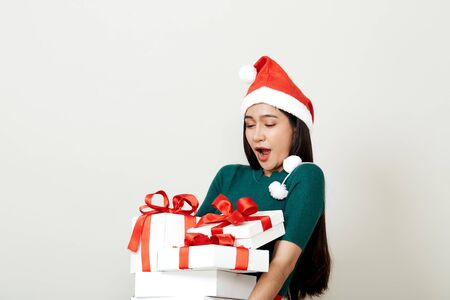 Foto de Beautiful Asian woman in in santa hat with many gifts studio shot isolated on bright gray background, copy space for text, Christmas Concept and new year - Imagen libre de derechos