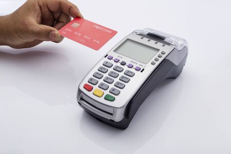 Photo pour Close up of Male holding in hands wireless modern bank payment terminal to process acquire credit card payments, red card isolated on white background. Copy space for financial advertising - image libre de droit