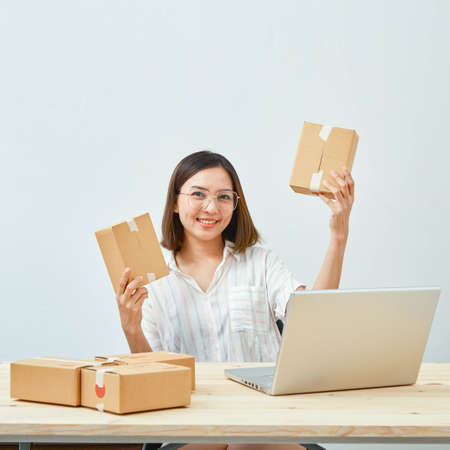 Foto de asian girl freelancer business private working at home office with holding tablet, laptop, note, packaging delivery online market on purchase orders to customer - Imagen libre de derechos