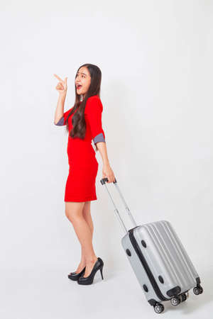 Photo pour A businesswoman in a red dress with a suitcase on white background, travel concept - image libre de droit