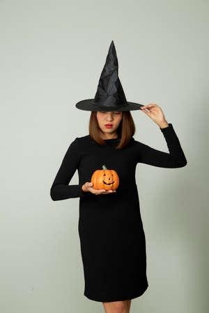Foto de Halloween holiday background. Young pretty woman in witch hat holding halloween pumpkin jack o lantern decor - Imagen libre de derechos