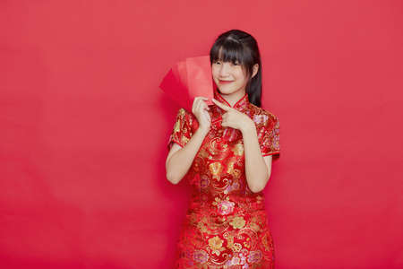 Photo pour Portrait beautiful young Asian Cute woman wear Chinese dress with Ang Pao or red letter with cash for Chinese new year concept on red isolated background - image libre de droit