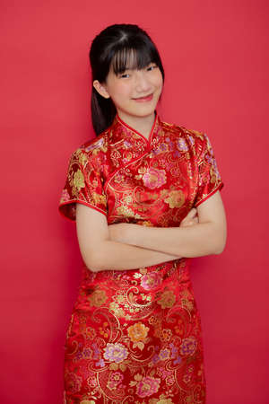 Photo for Cute young Asian woman wear cheongsam with action for Chinese new year concept on a red background - Royalty Free Image
