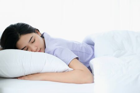 Photo pour Young beautiful Asia woman sleeping and enjoy on the soft bed at the modern bedroom and feeling relaxing in the morning. Hugging soft white pillow. Resting, good dream and sleep concept. - image libre de droit