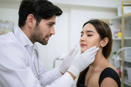 Foto de Doctor in uniform wearing glove and touch woman face. Check skin before plastic surgery in the clinic. Cosmetology and skin care concept. Lightening and smoothing wrinkles on the face skin - Imagen libre de derechos