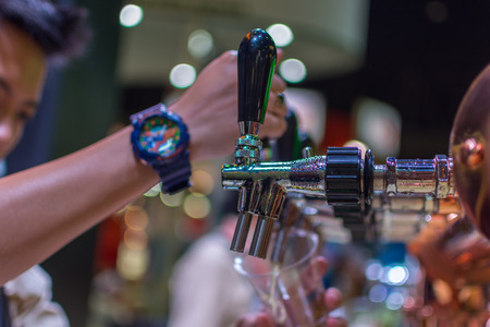 Barman or bartender pouring a draught lager beer from beer tap on counter for serving in a restaurant or pub.