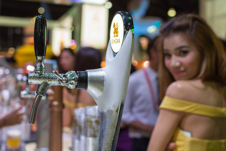 Bangkok, Thailand - May 28, 2016 : Unidentified barman or bartender pouring a draught lager beer from beer tap on counter for serving in a restaurant or pub.