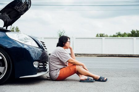 Photo pour Asian woman 40s alone driver checking a car engine for fix and repair problem with unhappy and dismal between waiting a car mechanic from car engine problem at roadside - image libre de droit