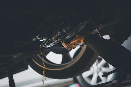 Foto de Car mechanic drain the old automatic transmission fluid (ATF) or gear oil at car garage for changing the oil in a gear box of car engine - Imagen libre de derechos