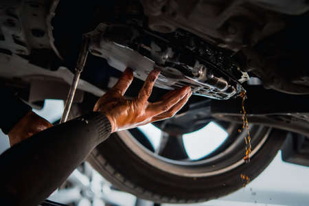 Photo pour Car mechanic drain the old automatic transmission fluid (ATF) or gear oil at car garage for changing the oil in a gear box of car engine - image libre de droit