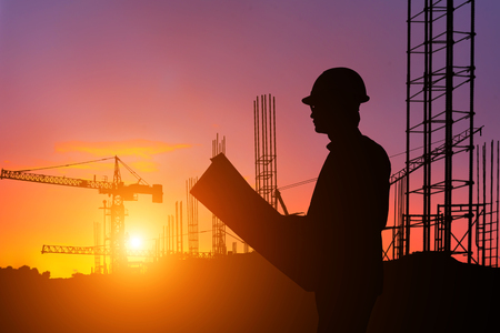Photo for Silhouette engineer looking construction worker in a building site at sunset - Royalty Free Image