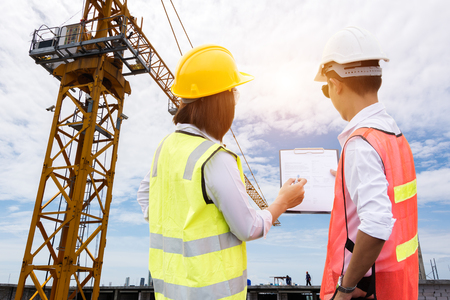 Photo for Teams engineer looking blueprint in a building site over Blurred construction site film grain progress and potential concepts. - Royalty Free Image