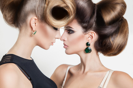Portrait of two sexy women in studio with volume creative hairstyle looking at each others in studio