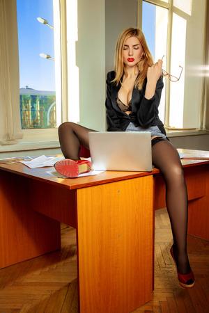Photo pour Gorgeous lustful secretary with laptop between the legs. Business concept - image libre de droit