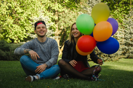 funny couple sits on the grass with a lot of colorful balloons in female hands and having fum