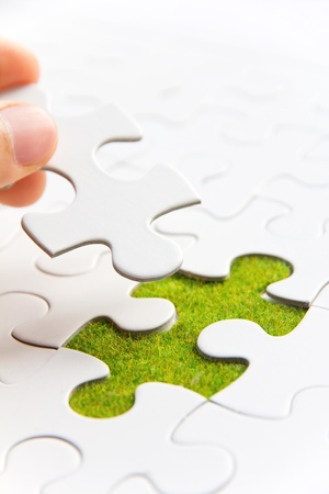 Photo for Hand embed missing puzzle piece into place, green space concept - Royalty Free Image