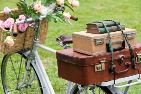 Vintage bicycle on the field with a basket of flowers and bag