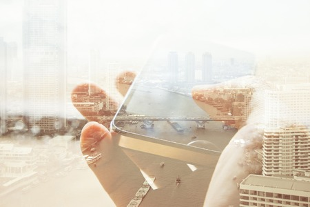 Double exposure of cityscape and smart phone, business technology concept.