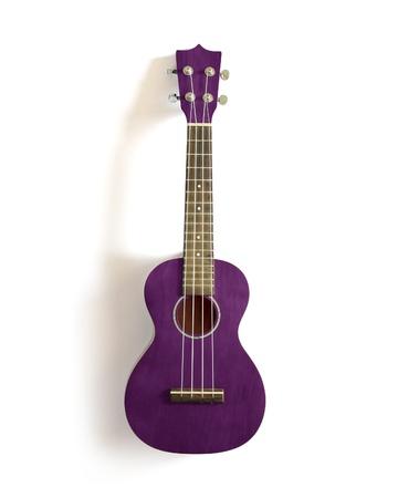 violet old ukulele on white isolated