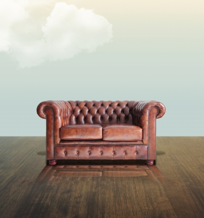 Classic Brown leather sofa on wood under the sky background.