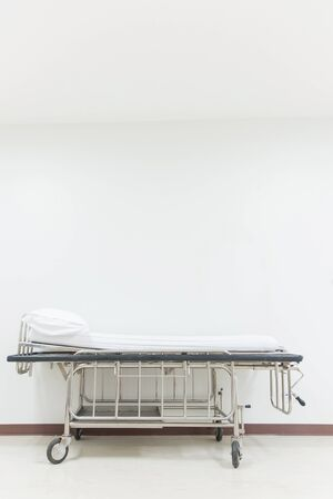 Empty stretcher trolley or hospital trolley waiting for patient with white room.