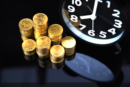 Coins stacks and alarm clock with tablet computer and financial graph, business planning vision and finance analysis concept idea.